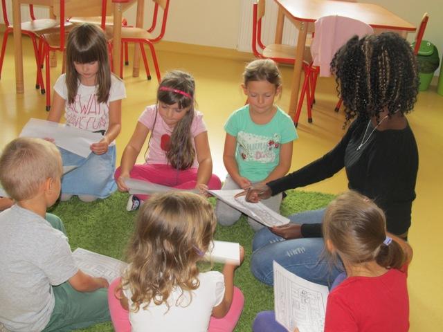 Rośnie liczna placówek edukacyjnych. Polacy chcą nowszych sposobów nauczania - dzieci  i kobieta siedzą na dywanie w kole.