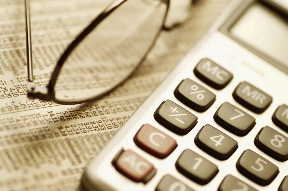 Dolar i funt w natarciu, euro w odwrocie - kalkulator i okulary leżą na stole na dokumentach