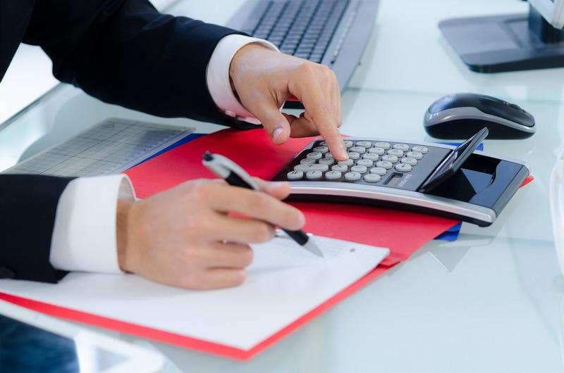 Opodatkowanie wynagrodzeń - reforma zabije klasę średnią  - mężczyzna siedzi przy biurku i liczy na kalkulatorze