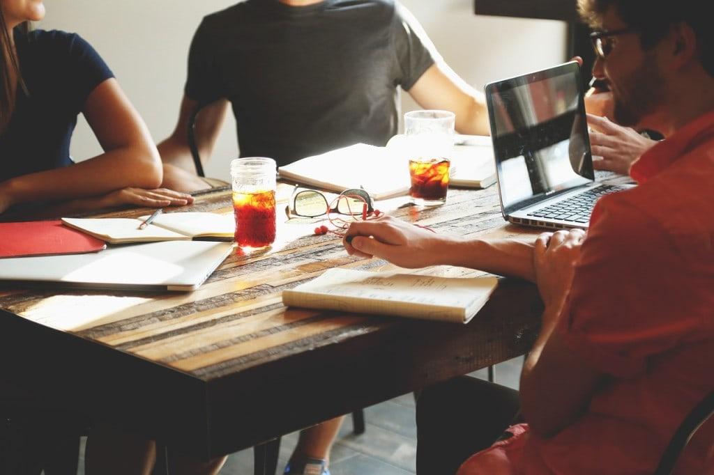 MŚP w kryzysie - Google.org i Youth Business Poland pomagają - kobiety i mężczyźni i kobieta siedzą przy stole, na którym leza dokumenty i stoi laptop oraz herbata