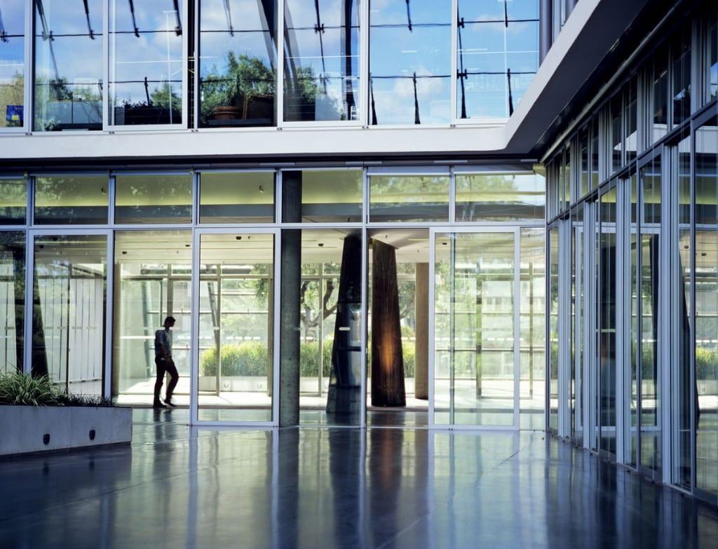 Konflikt ze społecznym inspektorem pracy może się skończyć karą dla pracodawcy - mężczyzna idzie korytarzem biurowca.