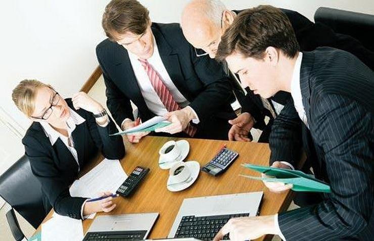 Tarcza dla branż - ZPP ocenia projekt - kobieta i trzech mężczyzn siedzą przy biurku i patrzą w monitor laptopa.