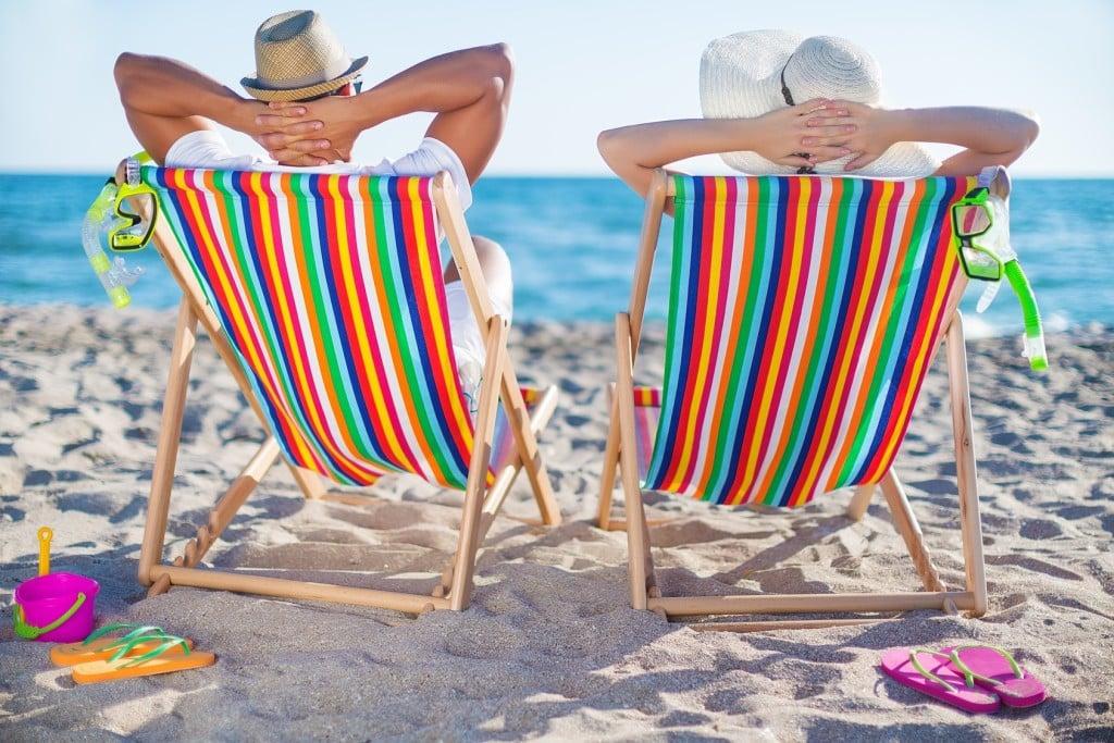 LOT na wakacje - do wyboru ponad 100 atrakcyjnych połączeń -kobieta i mężczyzna siedzą na plaży na leżakach.