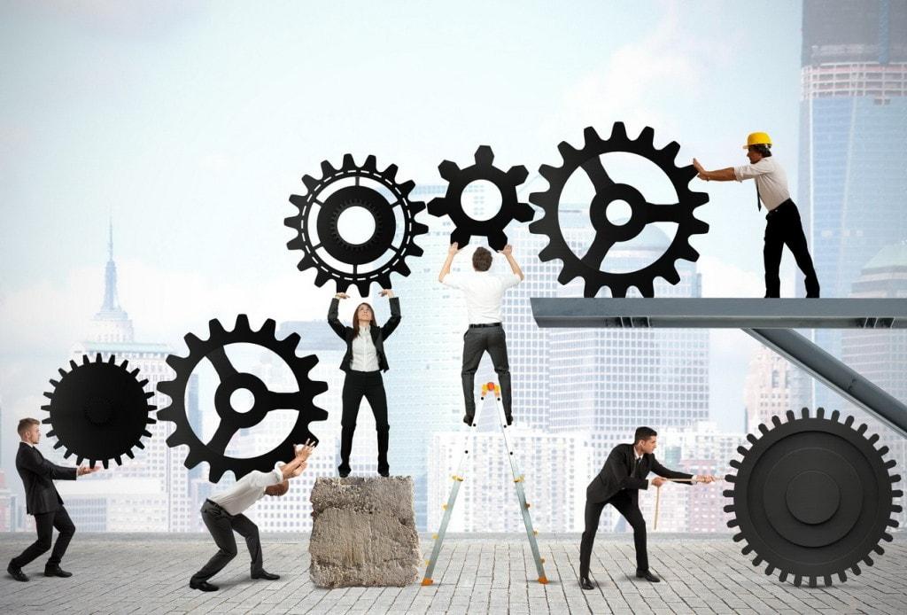 Mentoring, czyli uczeń i mistrz – nowoczesne zarządzanie - ludzie trzymają koła  zebate w rękach.