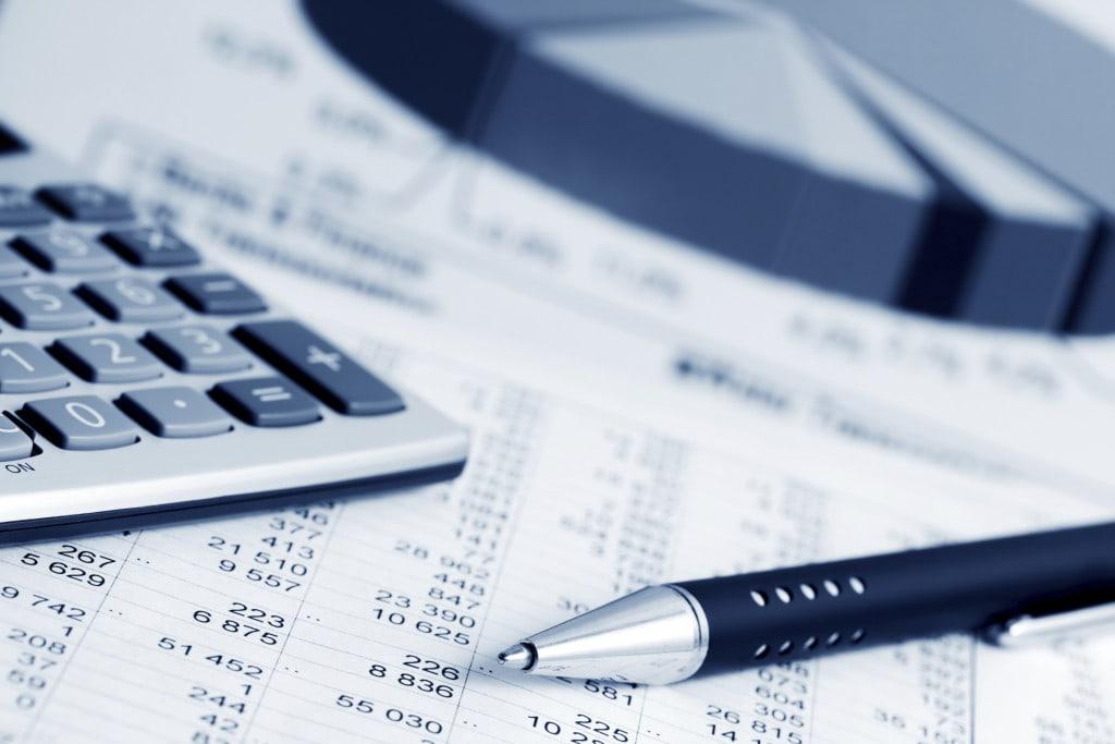 Krynica Vitamin hojnie dzieli się z inwestorami - wypłaci 18 milionów złotych zaliczki na dywidendę - dokumenty, kalkulator i długopis leżą na biurku.