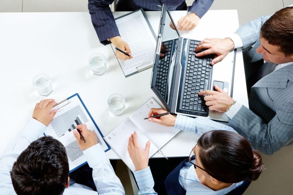 Pieniądze dla startupów z konkursu Poland Prize - ludzie siedzą przy stole w biurze z notatkami w rękach.