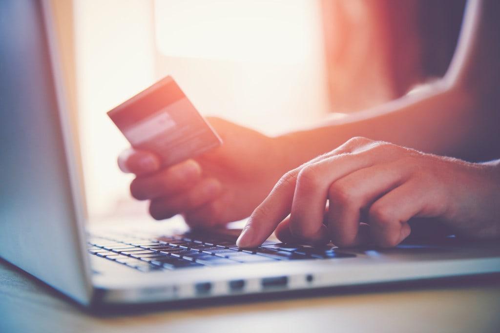 karta bankowa do płatności w Internecie - laptop dłonie i karta