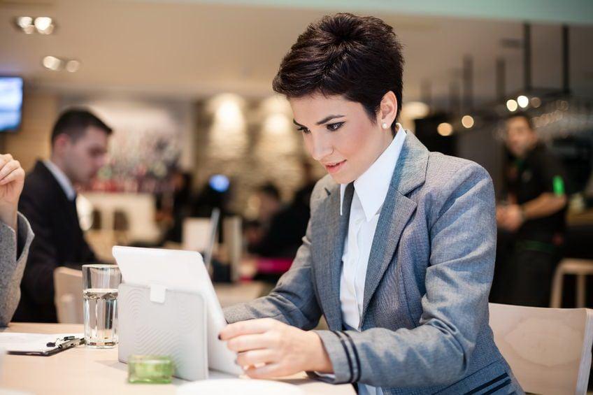Akademia Menadżera Innowacji szansą dla firm na wyjście z koronakryzysu - kobieta siedzi przy stole i pisze na tablecie.