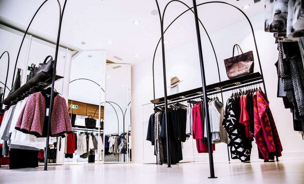 Dobra luksusowe i moda w pandemii - eleganckie ubrania wiszą na wieszakach w butiku odzieżowym.
