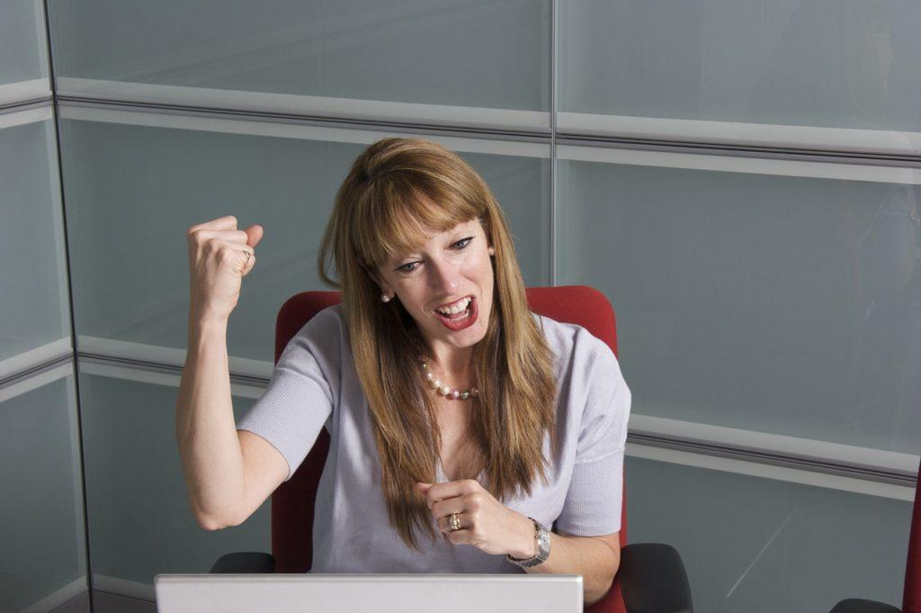Crafting, czyli jak podnieść satysfakcję z pracy -uśmiechnięta  kobieta siedzi przy biurku.