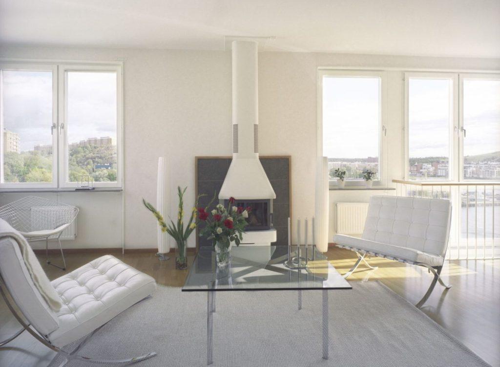 Rząd mądrze pomoże w zakupie mieszkania? - wnętrze salonu z kominkiem, fotelami i ławą w mieszkaniu w bloku.
