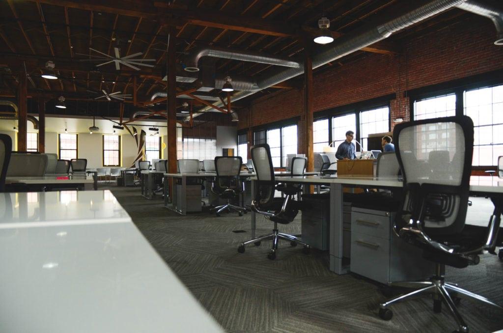 Bezrobocie w styczniu 2021 r. Kto został bez pracy? - przestrzeń biurowa z pustymi biurkami i krzesłami.