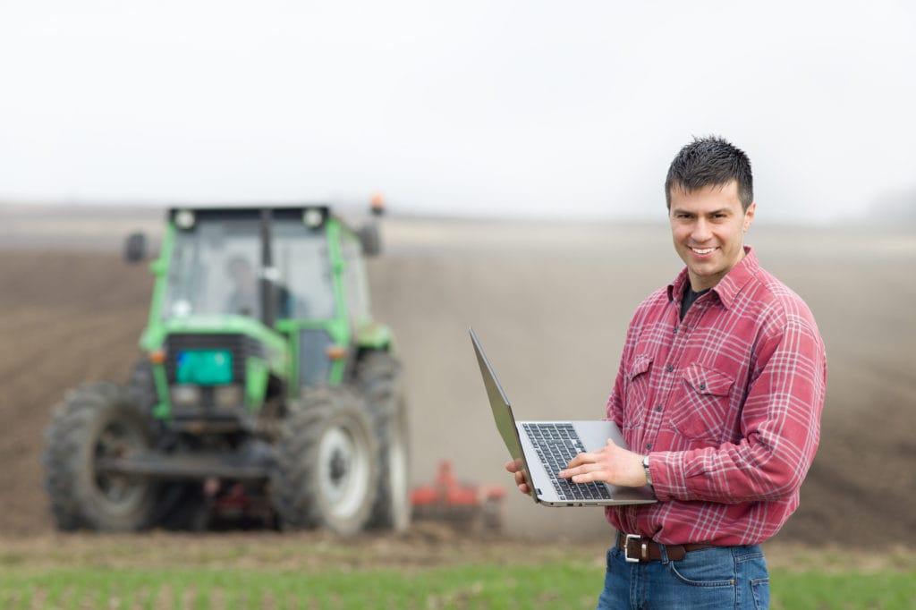 Zrównoważone rolnictwo - biznesowa szansa dla rolników i konsumentów  - mężczyzna stoi na polu z komputerem w reku, w tle traktor.