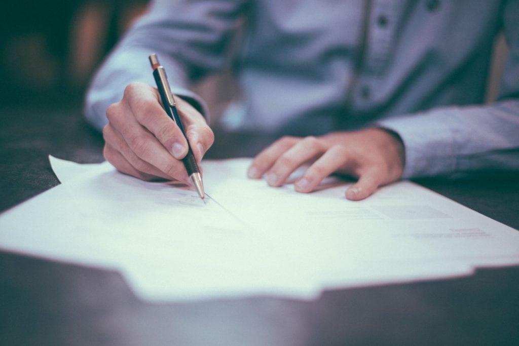 Raty kredytów pójdą w górę. RPP podniosła stopy procentowe - mężczyzna podpisuje dokumenty