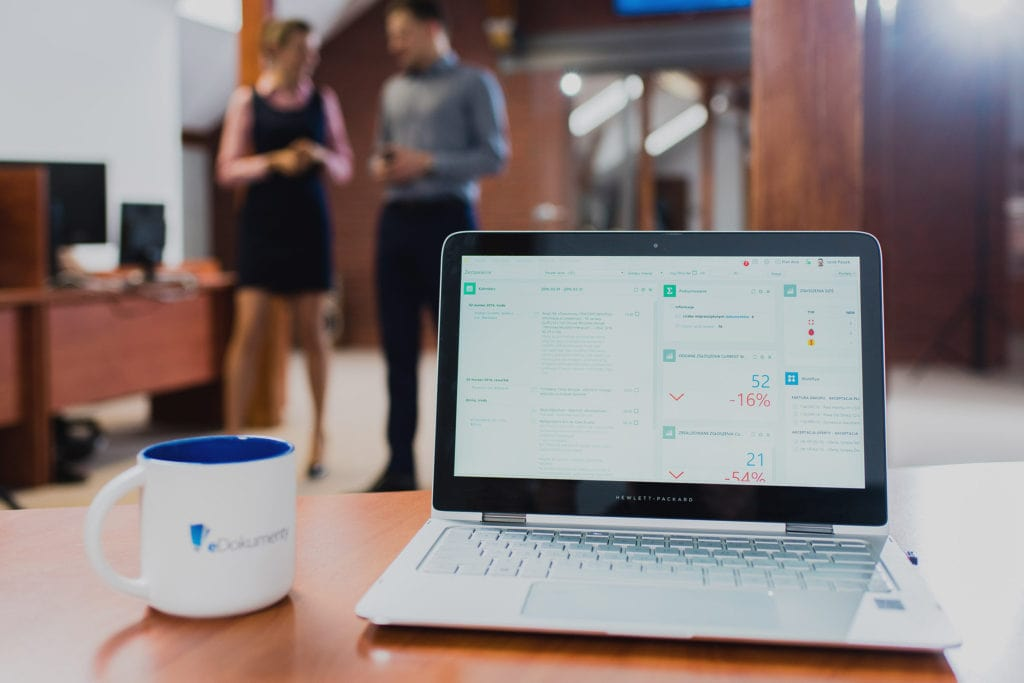Polacy nie boją się utraty pracy  - na biurku stoi laptop ze statystykami na ekranie.