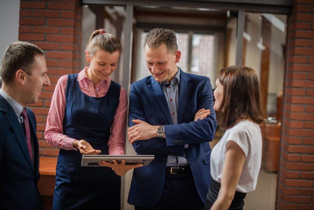 GPW uruchamia segment spółek rodzinnych - ludzie stoją na korytarzu i patrzą w ekran laptopa.