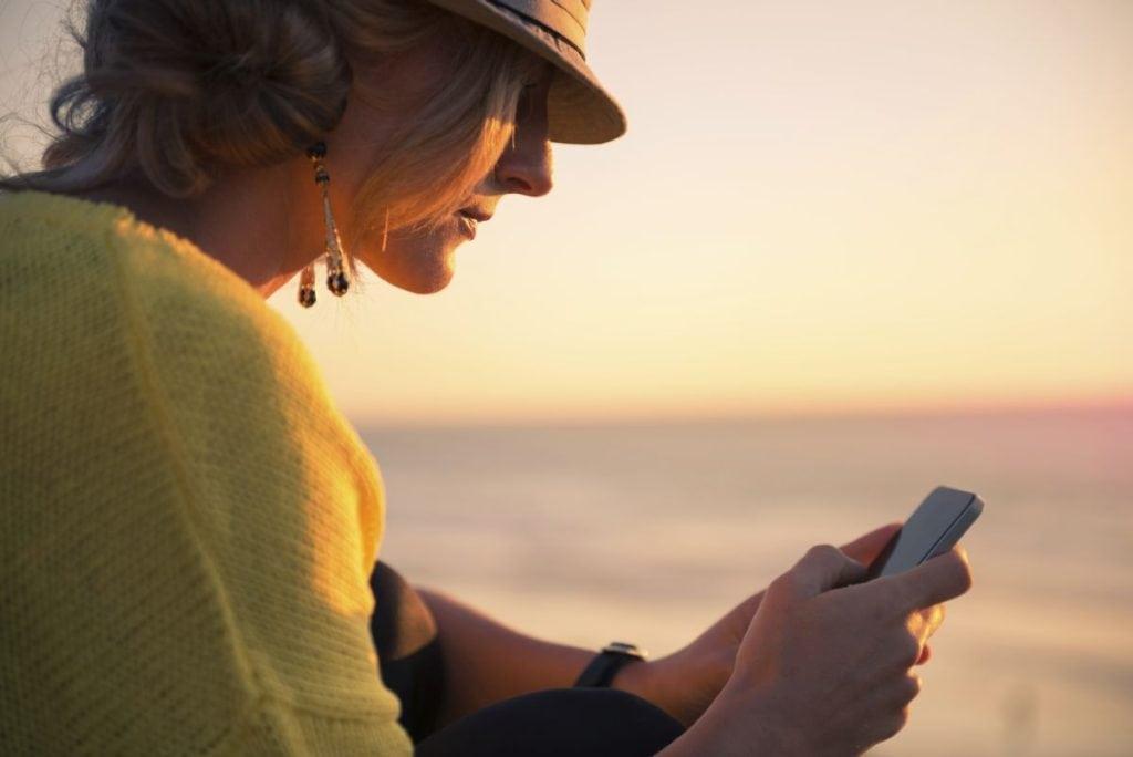 Miłość w czasach internetu - kobieta trzyma w ręku telefon