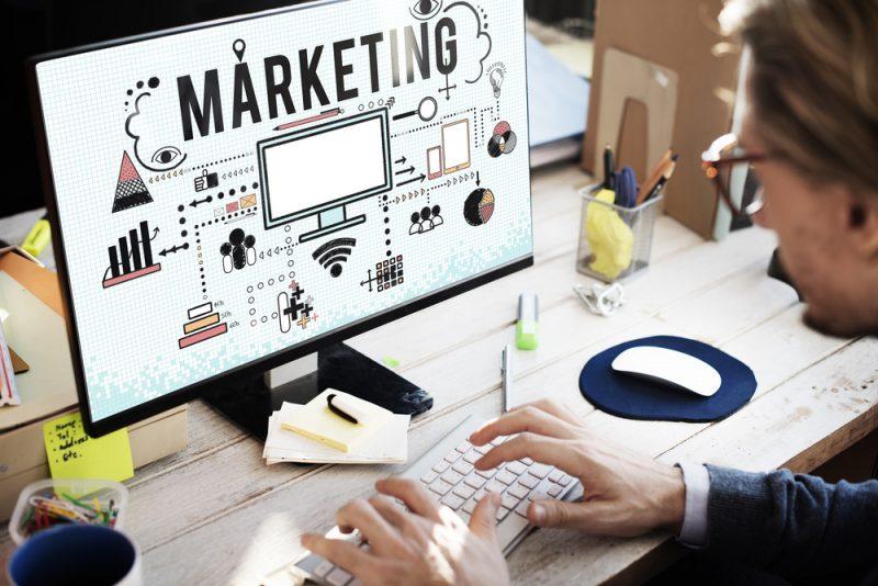 Marketing internetowy pomaga turystyce walczyć o klienta - mężczyzna pisze na klawiaturze komputera.