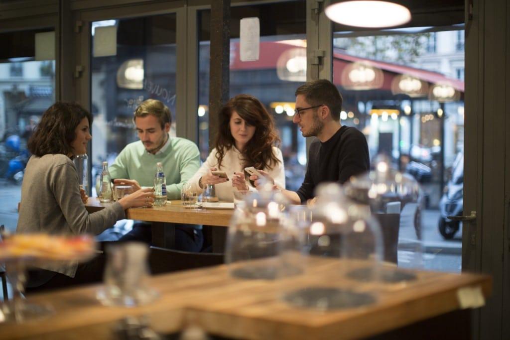 Polacy coraz mniej martwią się o zdrowie - ludzie siedzą przy stoliku w restauracji