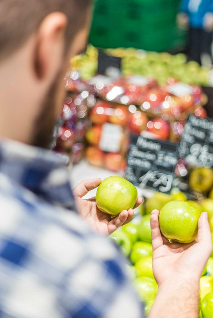 Prawie połowa Polaków robi zakupy na zapas- męzczyzna w sklepie trzyma w dłoniach jabłka.