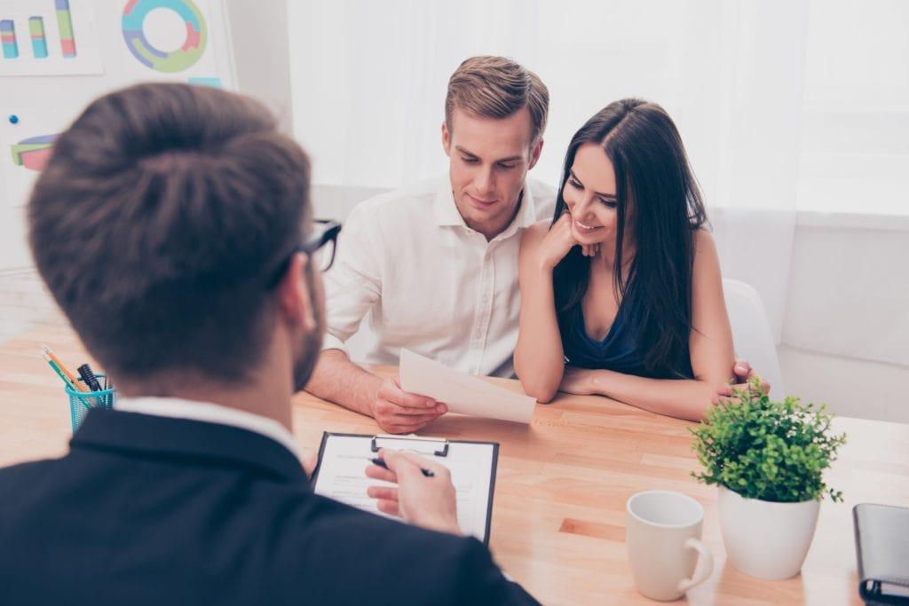 Życie na kredyt, czyli jak pożyczają Polacy - kobieta i mężczyzna czytają dokument siedząc w biurze przy biurku.