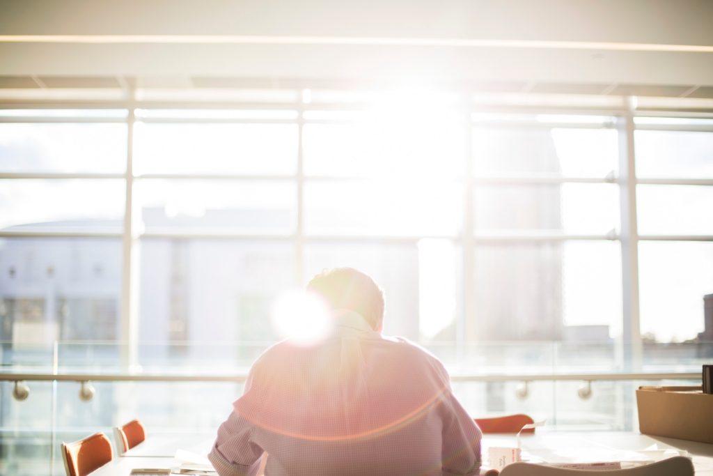 Polski Ład - wyższa kwota wolna od podatku zachęci do legalnej pracy - mężczyzna siedzi tyłem przy stole w budynku z widokiem na miasto.