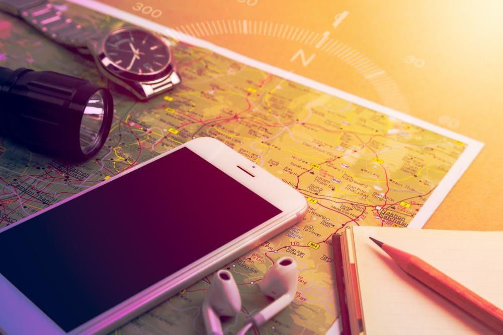 Bezpieczne podróże - praktyczne rady dla turystów - na stole leżą mapa, telefon, notes, zegarek i latarka.