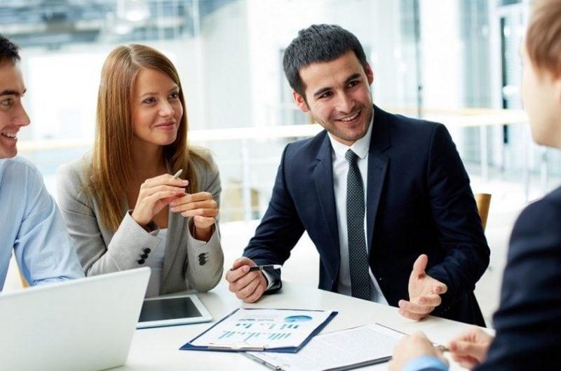 Employee Experience w praktyce, czyli jak budować pozytywne doświadczenia pracownika- ludzie siedza przy stole w biurze i rozmawiają.