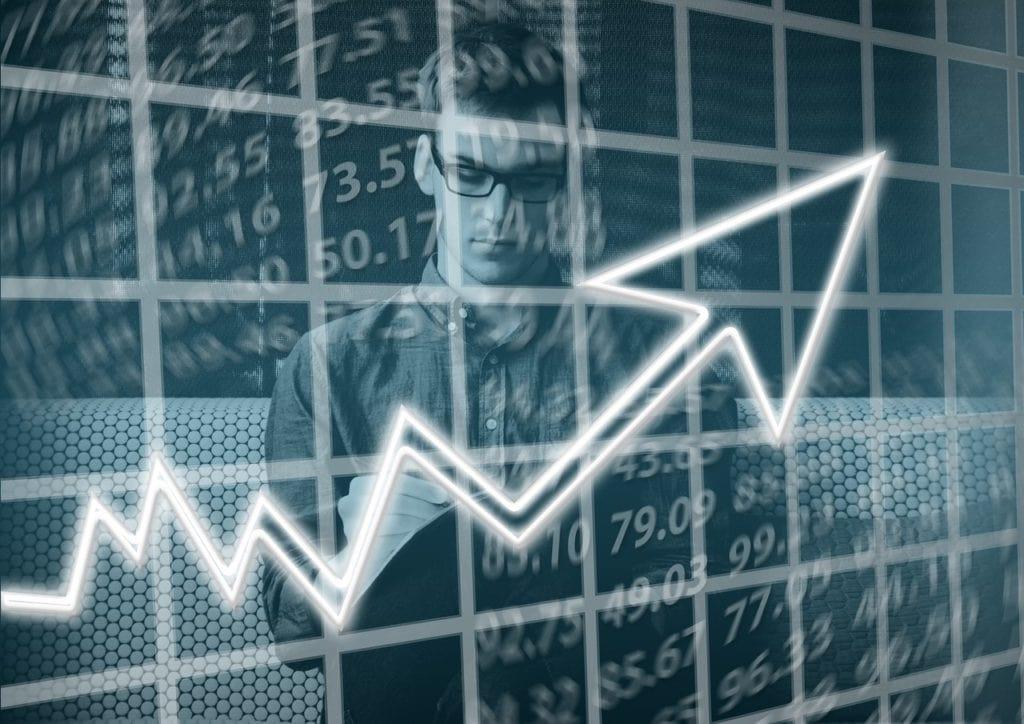 Fitch potwierdza dotychczasowy rating Polski - mężczyzna w okularach stoi na tle liczb