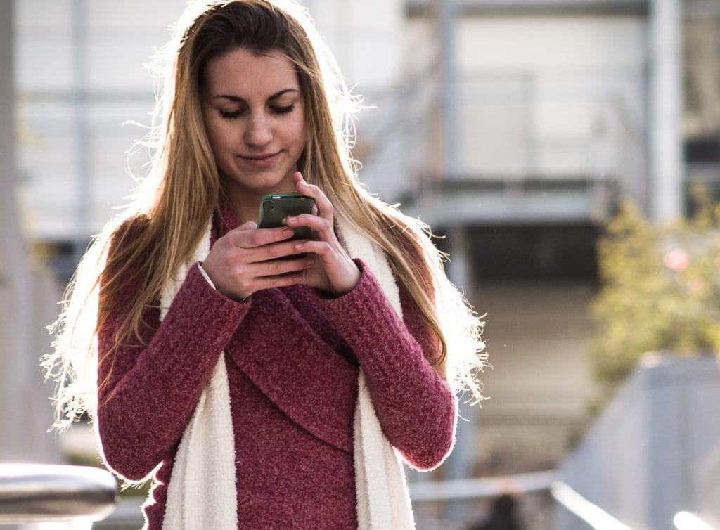 Innowacyjna aplikacja pomoże walczyć z przemocą w szkołach- kobieta na spacerze trzyma telefon w dłoni.
