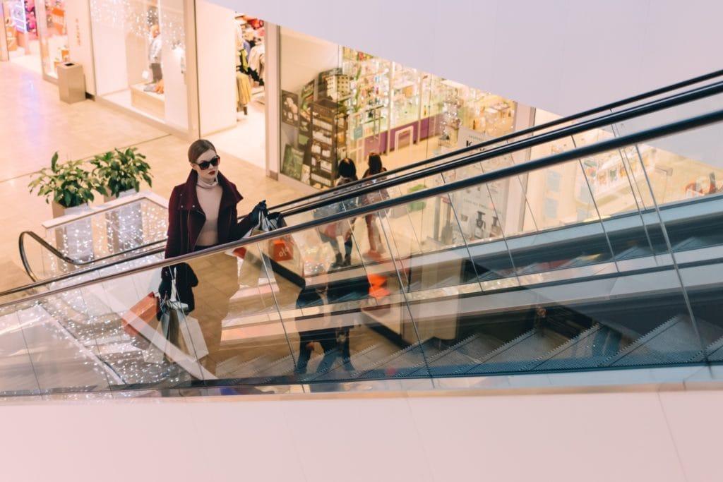 """Najemcy centrów handlowych """"zostają na lodzie""""? - kobieta na schodach ruchomych w centrum handlowym."""