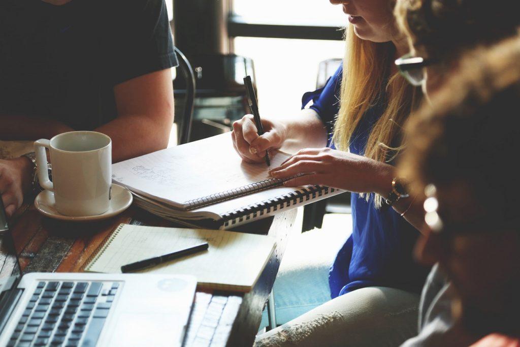 Innowacyjne startupy w MIT Enterprise Forum CEE-  ludzie siedzą przy stole, kobieta robi notatki w zeszycie, na stole stoi kubek.