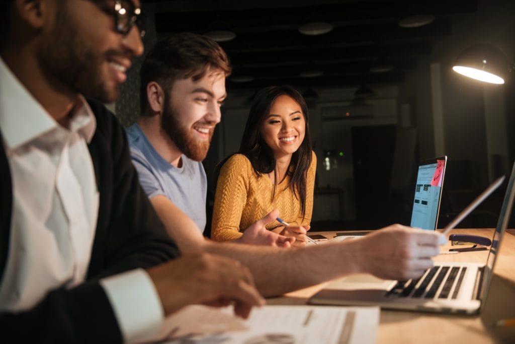 EXPO 2020 – MŚP przed szansą na promocję w Dubaju - kobieta i dwóch mężczyzn siedzą przy biurku przed otwartym laptopem.