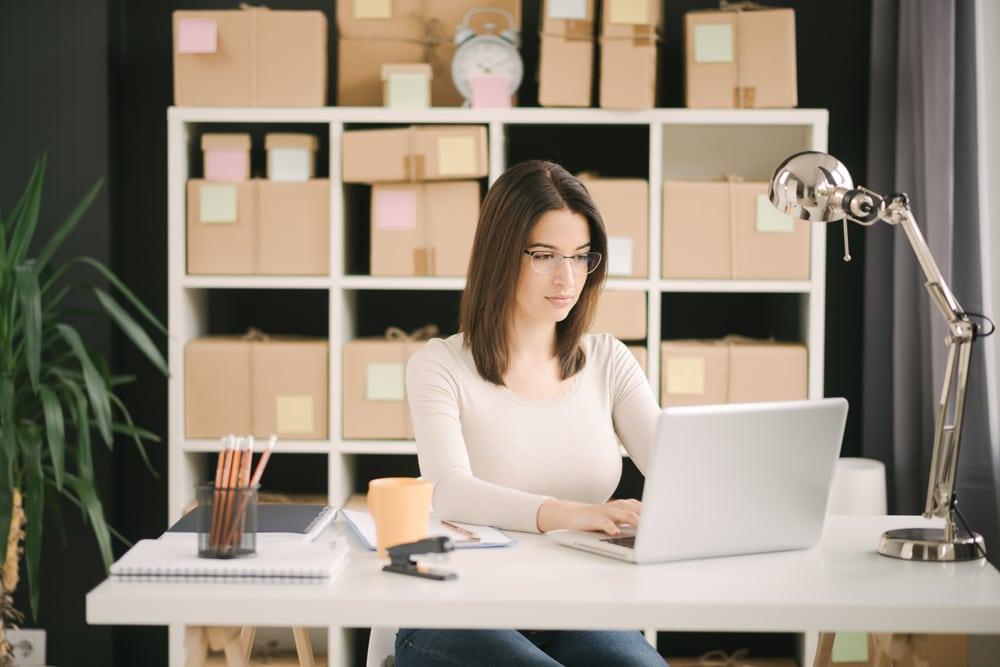 Jak będzie wyglądał handel w 2021 roku? - kobieta siedzi przy biurku i pisze na klawiaturze laptopa.