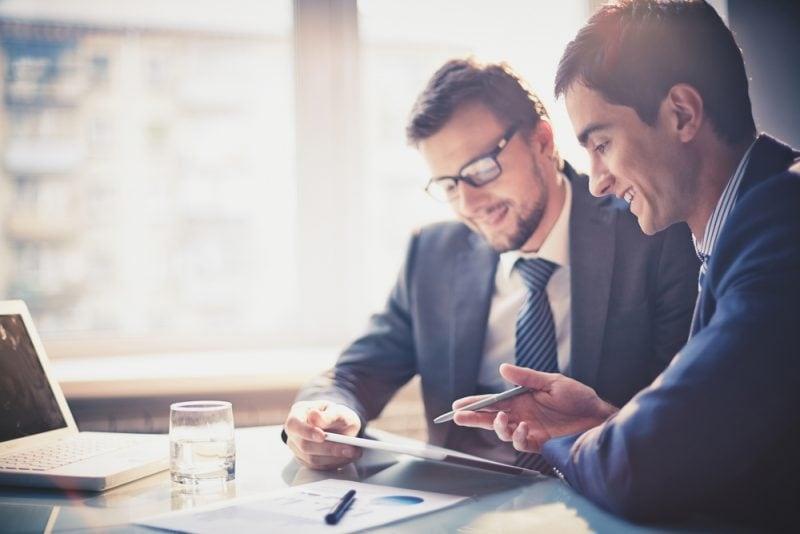 """""""Go to Brand – Expo 2020"""" w Dubaju - ruszył nabór wniosków - dwóch mężczyzn w biurze siedzi przy biurku z tabletem w rękach."""