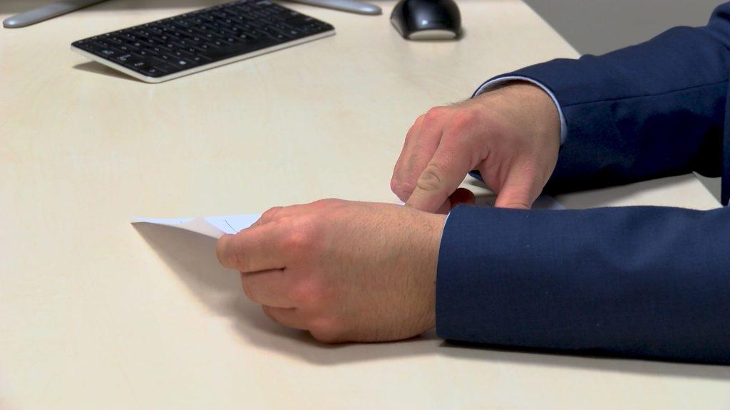 Koszt zwolnienia pracownika - dokumenty w męskich dłoniach