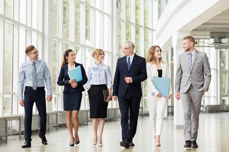 Dyrektorzy finansowi prognozują rozwój rynku fuzji i przejęć - kobiety i mężczyźni idą korytarzem biurowca.