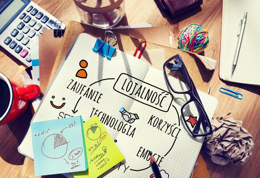 W pandemii wzrasta znaczenie działów marketingu -na biurku leżą zeszyt, małe karteczki, zeszyt i długopis.