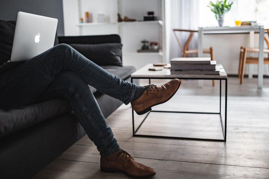 Polski Ład obciąży wynajmujących mieszkania i lokale - mężczyzna siedzi na kanapie w mieszkaniu z laptopem na kolanach.