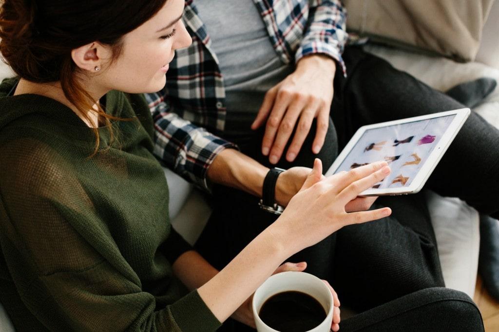 Jak ustalić bezpieczne hasło w sieci? - kobieta i mężczyzna siedzą na kanapie i trzymają tablet w rękach.