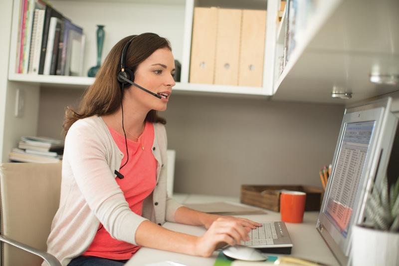 Praca zdalna, czyli obsługa klienta w czasach zarazy - kobieta przy biurku pracuje w domu