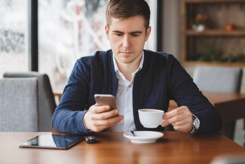 Rusza BLIKOMANIA: każda transakcja to szansa na wygraną - meżczyzna siedzi przy stoliku w kawiarni, pije kawę, w reku trzyma telefon.