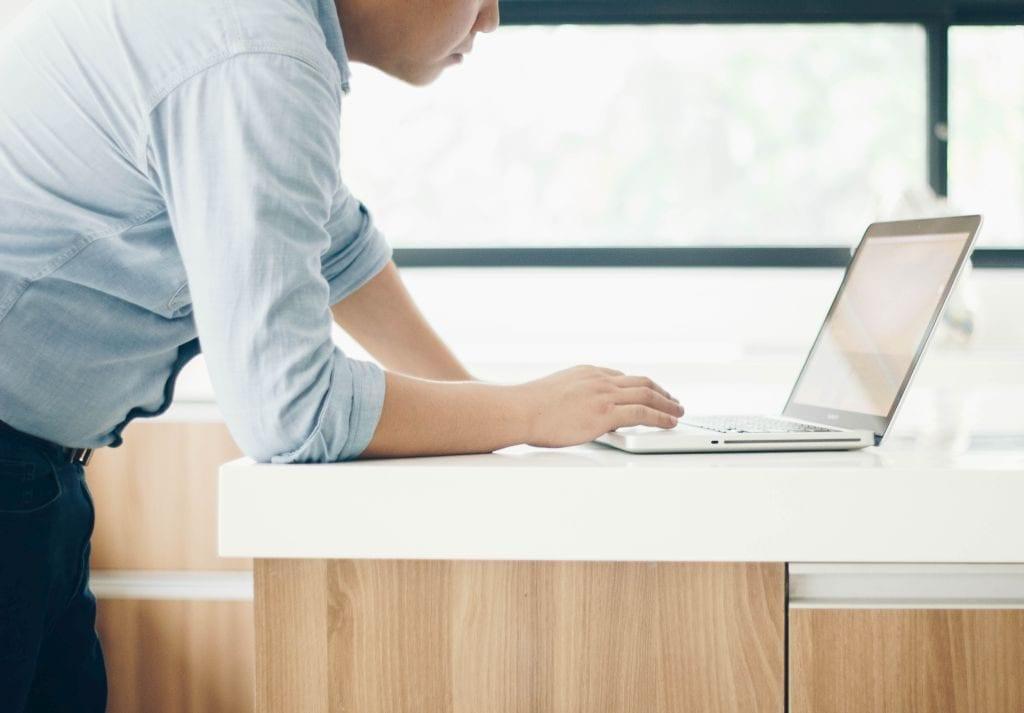 Wniosek o pozwolenie na budowę złożysz przez internet już od 1 lipca- mężczyzna nachylony nad laptopem.