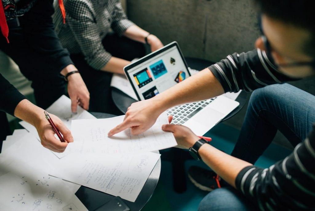 Pieniądze dla przedsiębiorców, którzy powracają do biznesu - ludzie siedzą przy stole przy otwartych laptopach.