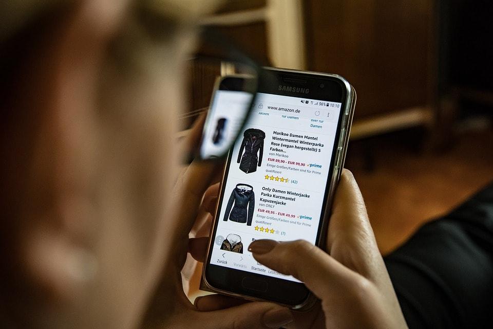 Czy zakupy przez urządzenia mobilne wygryzły zakupy tradycyjne? - kobieta trzyma w ręku telefon.