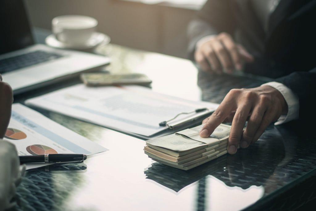 Płace rosną coraz szybciej -męska dłoń podaje plik pieniędzy.