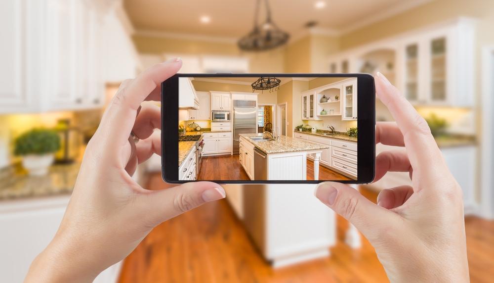 Jak zmiany prawne w Polskim Ładzie wpłyną na branżę nieruchomości? - kobieta robi robi zdjęcie telefonem kuchni.