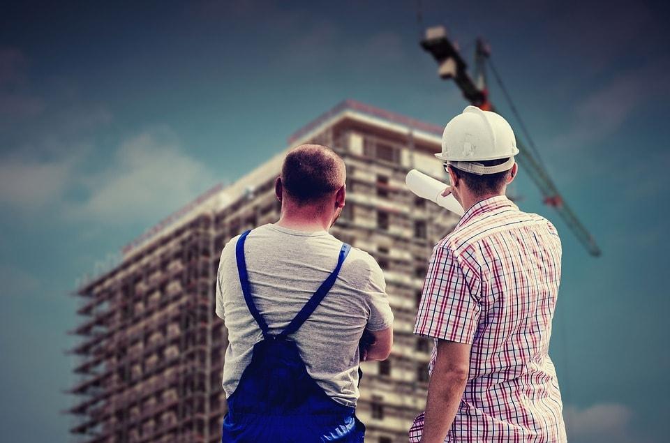 Gospodarka nie poradzi sobie bez cudzoziemców - dwóch pracowników na budowie patrzy na wysoki budynek.