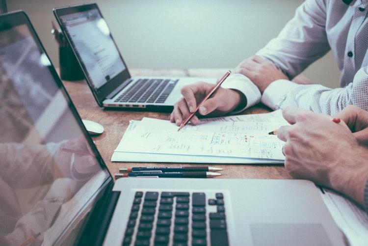 Restrukturyzacja - co krajowi przedsiębiorcy wiedzą o przekształceniu firmy - dwóch mężczyzn siedzi przy biurku przed otwartymi laptopami i notują w notesie.