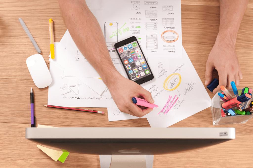 PARP oraz infuture.institute: startupy nadążają za trendami - mężczyzna siedzi przy biurku i pisze na kartkach kolorowymi pisakami.